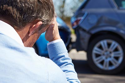 man looking at a car accident